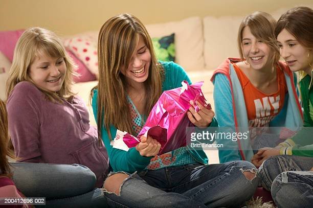 teenage girls (13-17) watching friend unwrap present, smiling - opening party stock photos and pictures