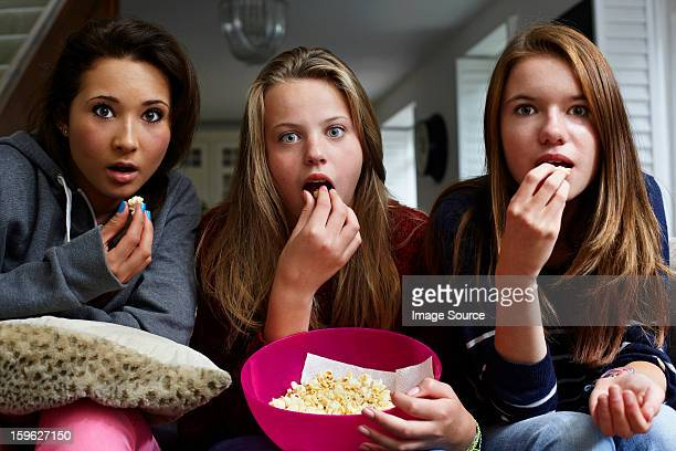teenage girls watching horror movie with popcorn - epic film foto e immagini stock
