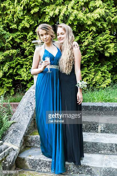 teenage girls wearing prom dresses holding champagne flute looking at camera smiling - prom dress stock pictures, royalty-free photos & images