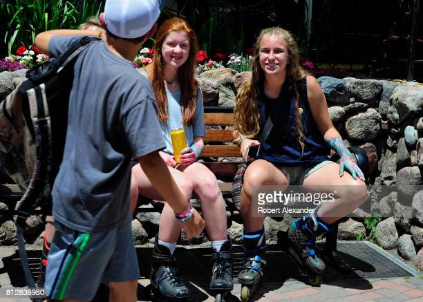 Teenage girls wearing roller blades smile at a passing boy in Vail Colorado