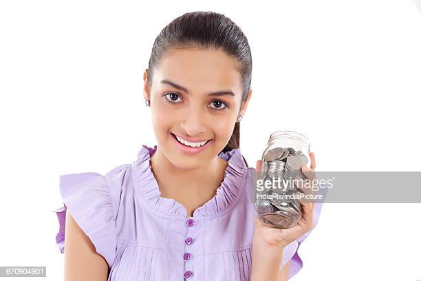 A Teenage Girls With A Jar Filled With Coins