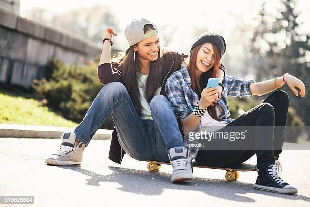 Teenager-Mädchen mit einem Handy und Skateboard