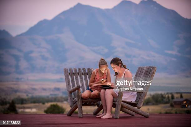 Teenage girls with devices on outside deck