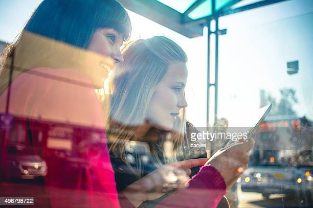 Teenage girls with digital tablet on the bus station