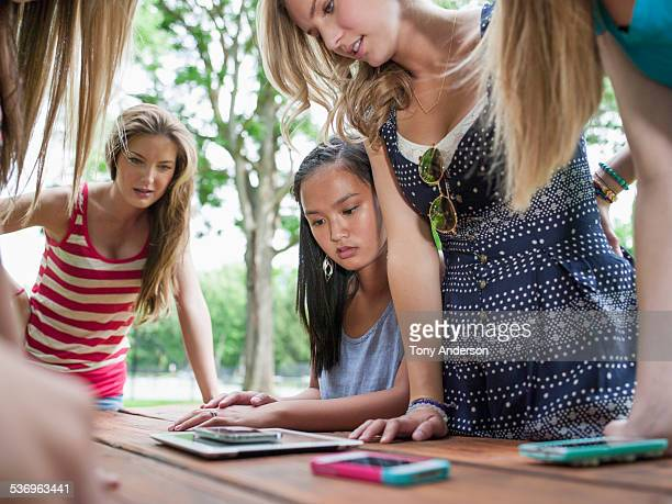Teenage girls with mobile devices outdoors