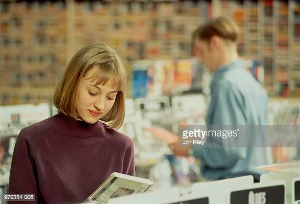 Teenage girl(16-18)standing behind rack in shop, looking at CD case