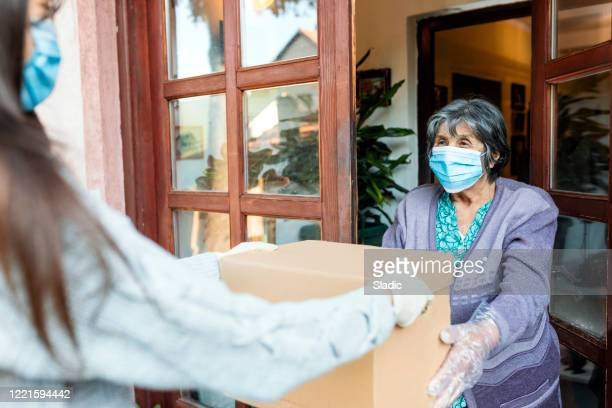 teenage girl,volunteer,delivering groceries to a senior woman, insulation,covid 19 - humanitarian aid stock pictures, royalty-free photos & images