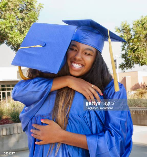 Teenage graduates hugging