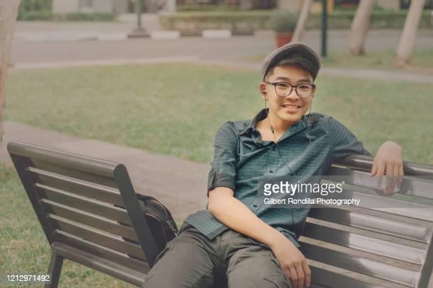 teenage guy sitting on park bench - filipijnen stockfoto's en -beelden