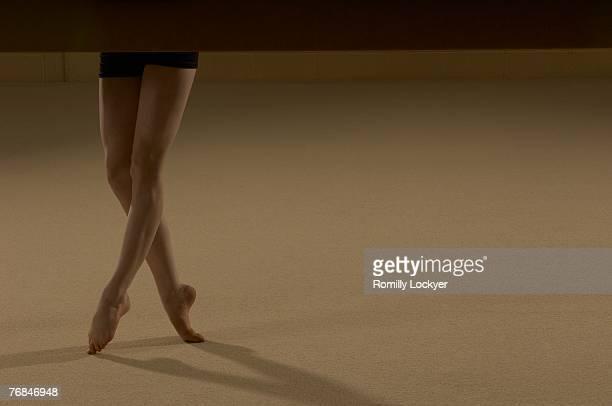 Teenage gymnast (16-18) balancing on toes, low section