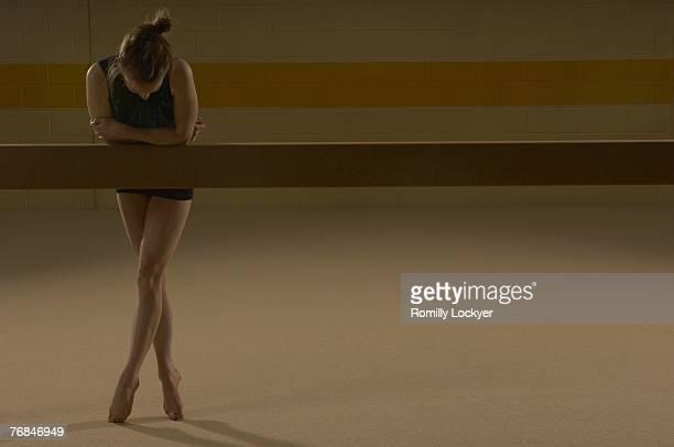 Teenage gymnast (16-18) leaning on balance beam