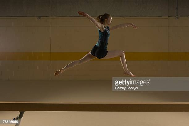 Teenage gymnast (16-18) leaping on balance beam