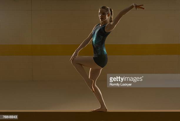 Teenage (16-18) gymnast performing on balance bar
