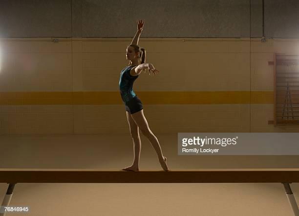 Teenage gymnast (16-18) performing on balance beam