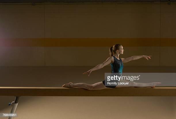 Teenage gymnast (16-18) performing splits on balance beam