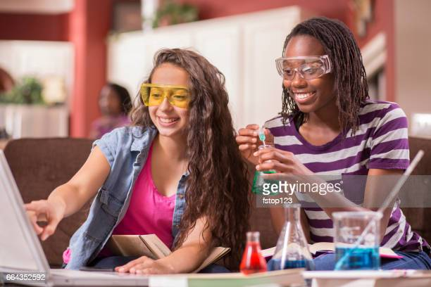 teenage high school girls studying science, chemistry at home. - minority groups stock pictures, royalty-free photos & images