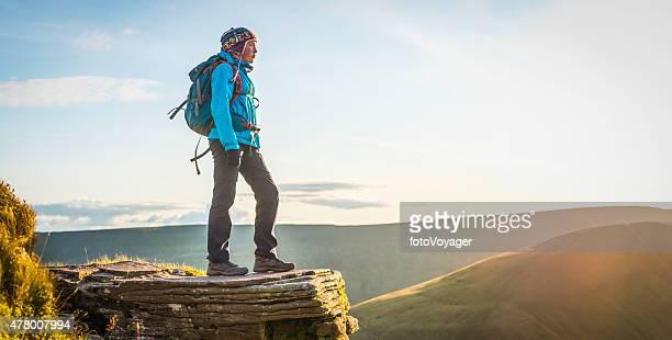 Teenage hiker on mountain ridge overlooking golden summer sunset panorama
