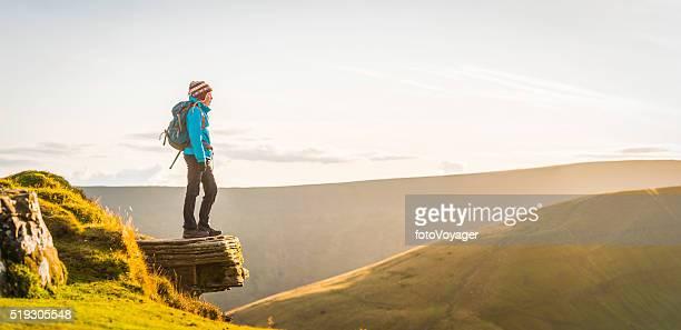 Adolescente randonneuse haut sur la montagne en pleine nature, surplombant le Panorama coucher de soleil doré