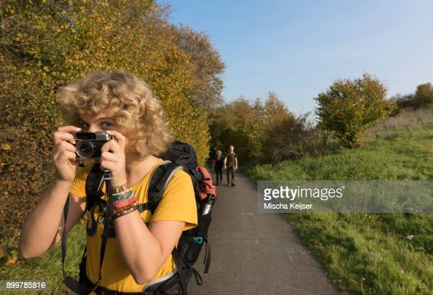 teenage hiker taking photo, family in background, meerfeld, rheinland-pfalz, germany - camera girls stock photos and pictures