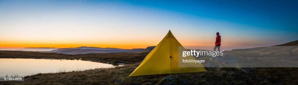 Teenage hiker wilderness c&ing yellow tent on mountain sunrise panorama  Stock Photo & Teenage Hiker Wilderness Camping Yellow Tent On Mountain Sunrise ...