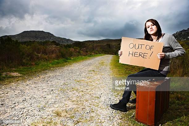 Adolescente hitchhiker con segno disperatamente per te