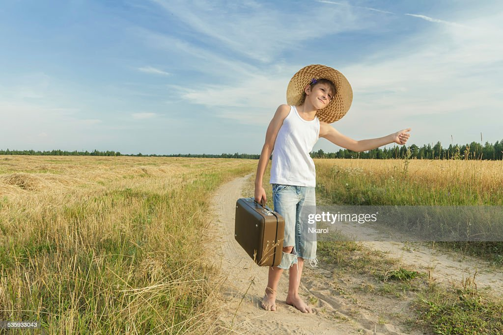 Teenage hitchhiking on country road : Stock Photo