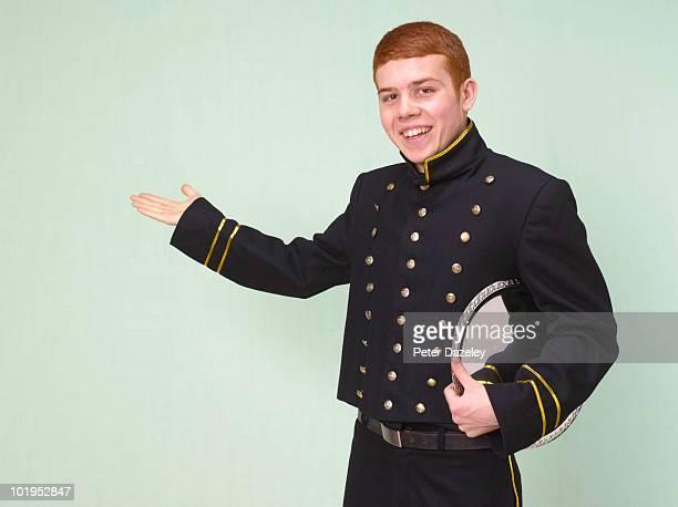 Teenage hotel bellboy bellhop welcoming