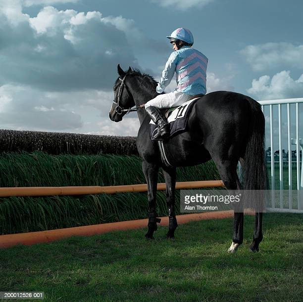 Teenage jockey (15-17) on horse in front of jump