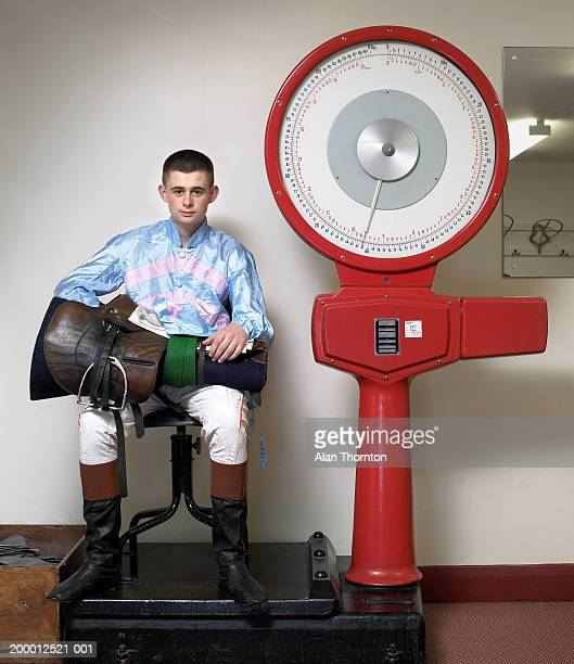 Teenage jockey (16-18) with  equipment weighing in, portrait