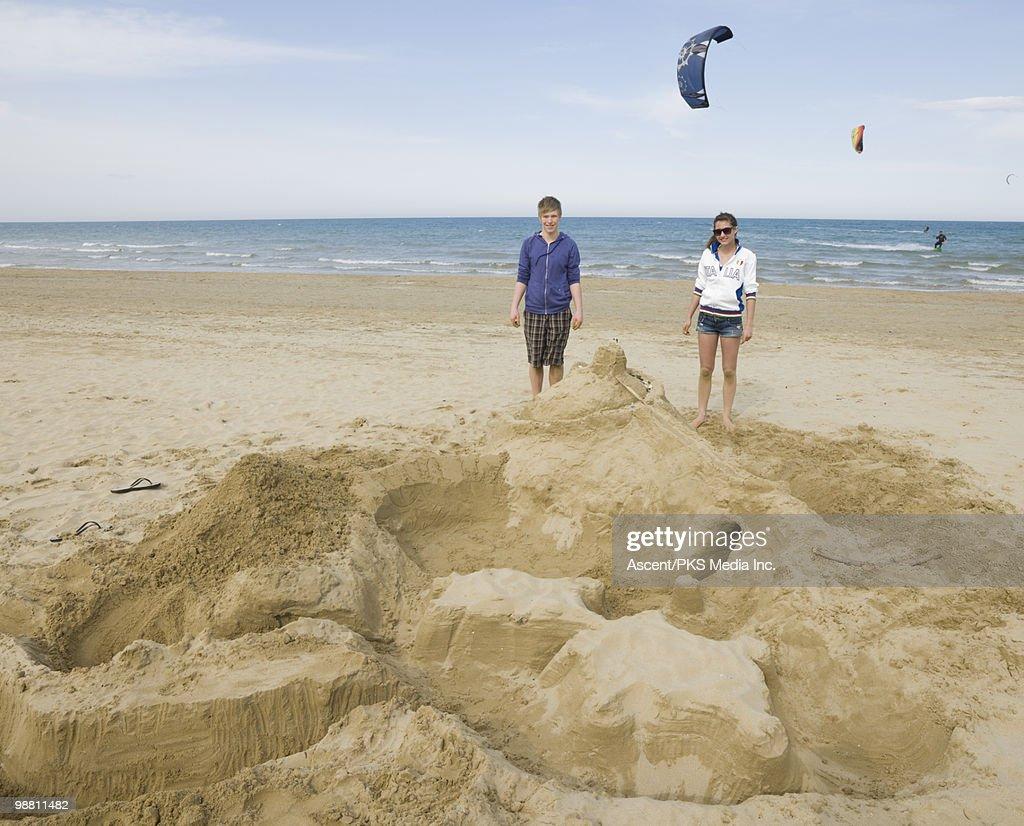 Teenage kids beside beach creation, kite surfers : Stock Photo