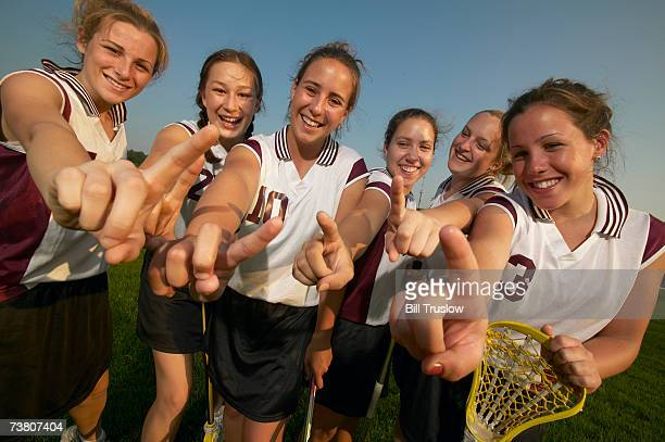 Teenage (16-17) lacrosse team signalling number one with fingers, group portrait