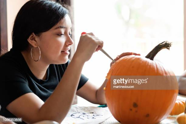 Teenage Latin American girl carving and decorating pumpkin for Halloween