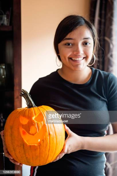 Teenage Latin American girl showing her carved pumpkin for Halloween