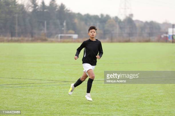 a teenage latino soccer player in his team uniform, runs on an outdoor soccer field. - sports uniform ストックフォトと画像