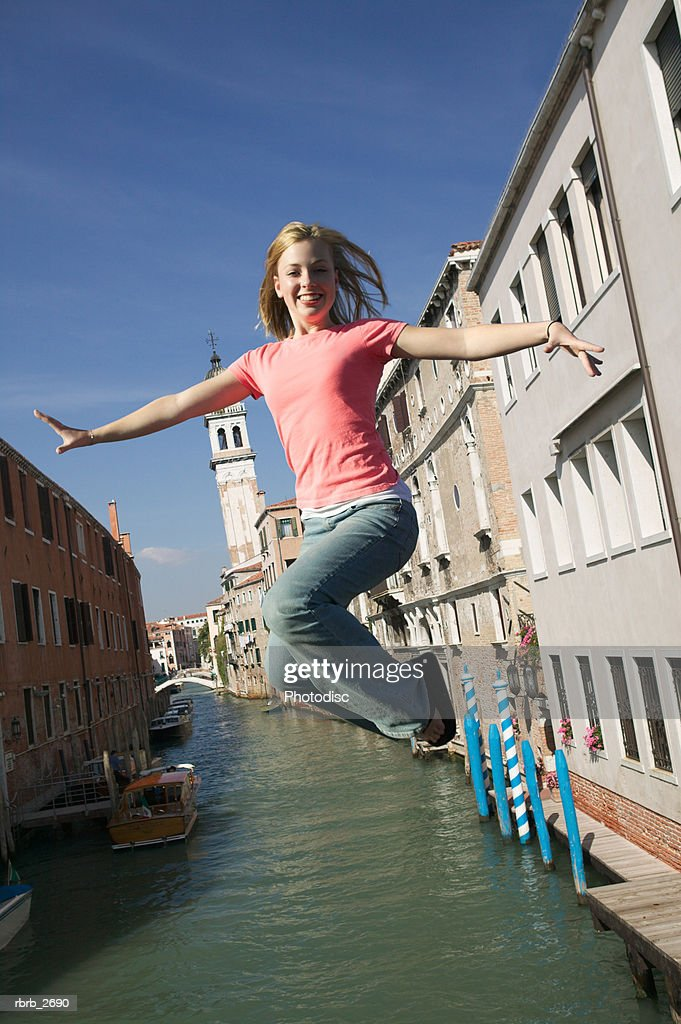 teenage lifestyle shot of a blonde female in a pink shirt as she jumps up over a canal : Foto de stock