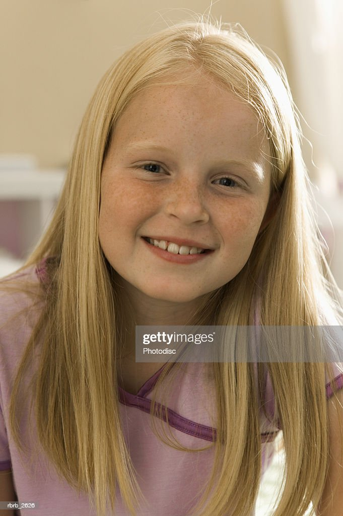 teenage lifestyle shot of a blonde girl in purple pajamas as she sits on her bed and smiles : Foto de stock
