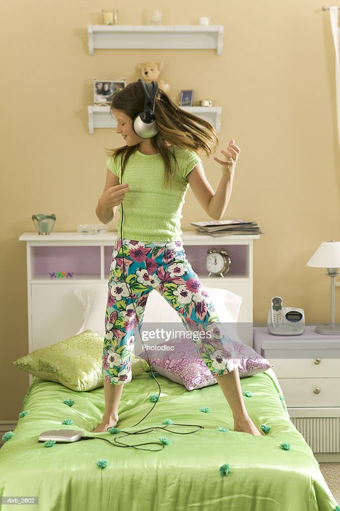 teenage lifestyle shot of a brunette girl as she listens to headphones and dances in her bedroom : Foto de stock