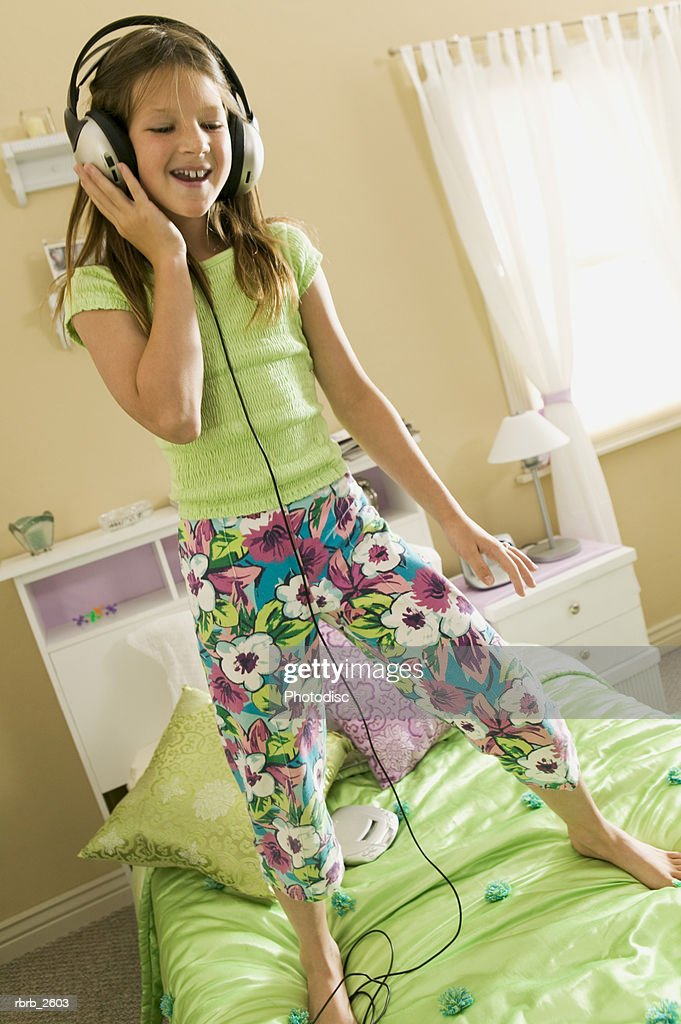 teenage lifestyle shot of a brunette girl as she listens to headphones in her bedroom : Foto de stock