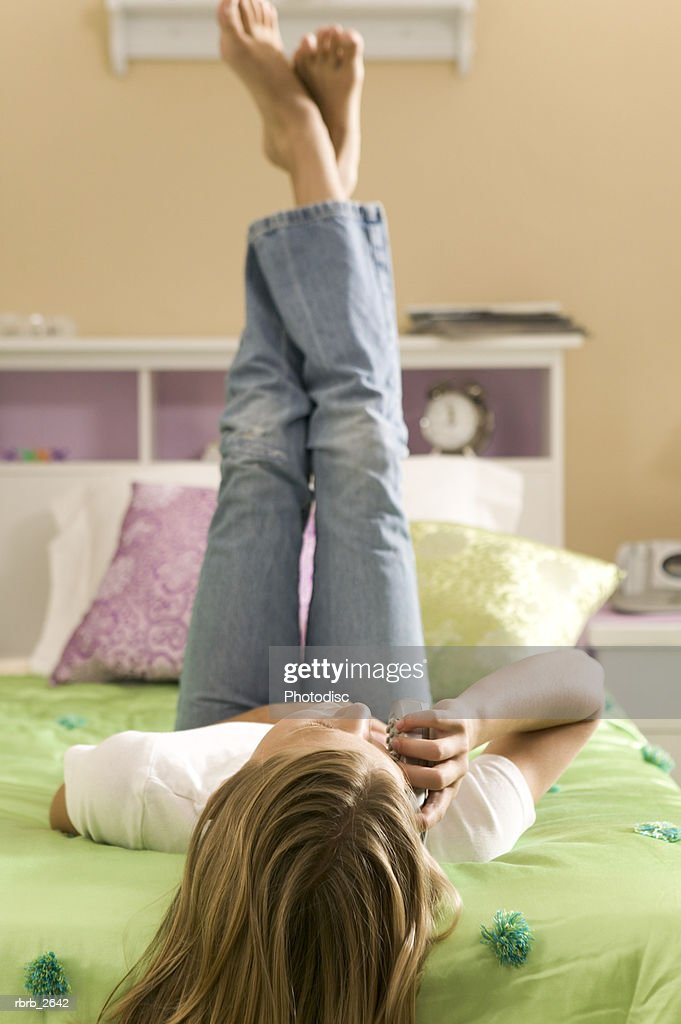 teenage lifestyle shot of a girl as she lays on the edge of her bed chatting on the phone : Foto de stock