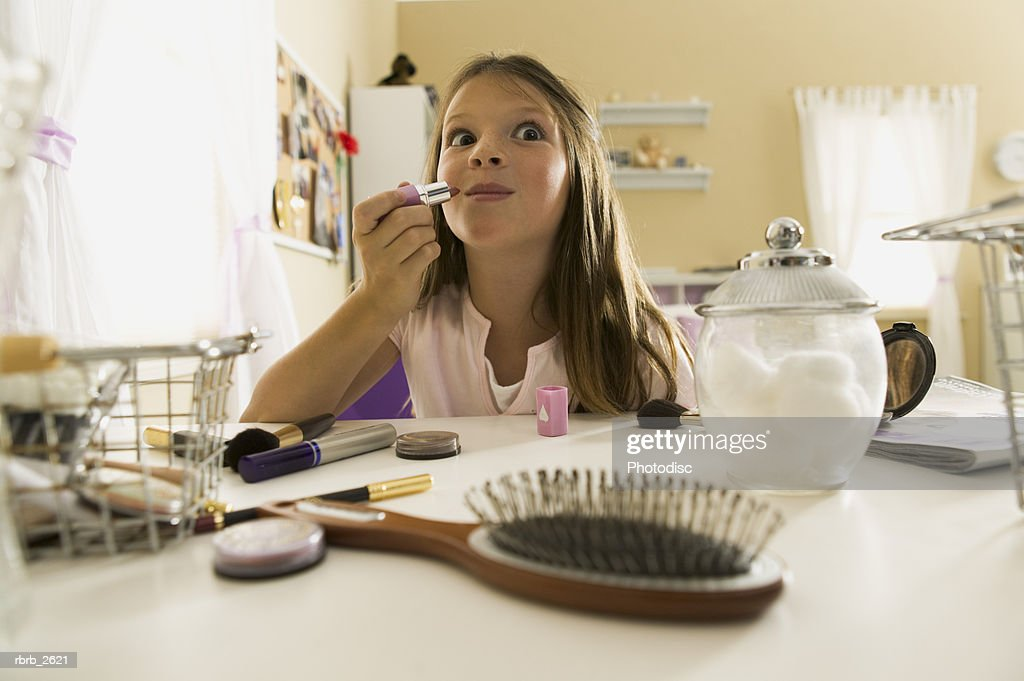 teenage lifestyle shot of a girl as she sits at a vanity and practices putting on lipstick : Foto de stock