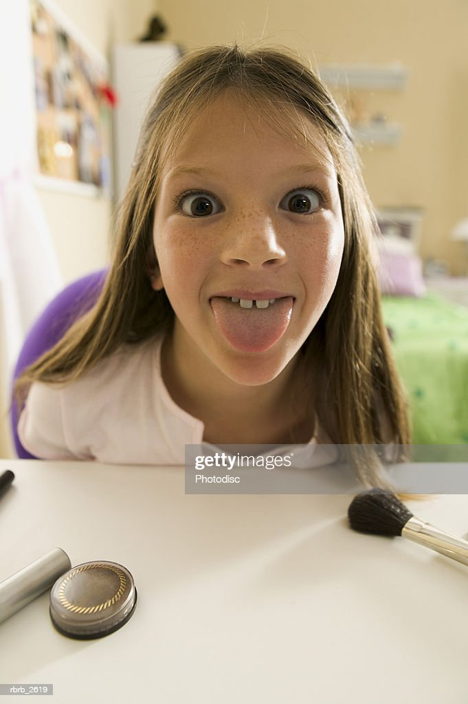 teenage lifestyle shot of a girl as she sits at a vanity and sticks out her tongue : Foto de stock