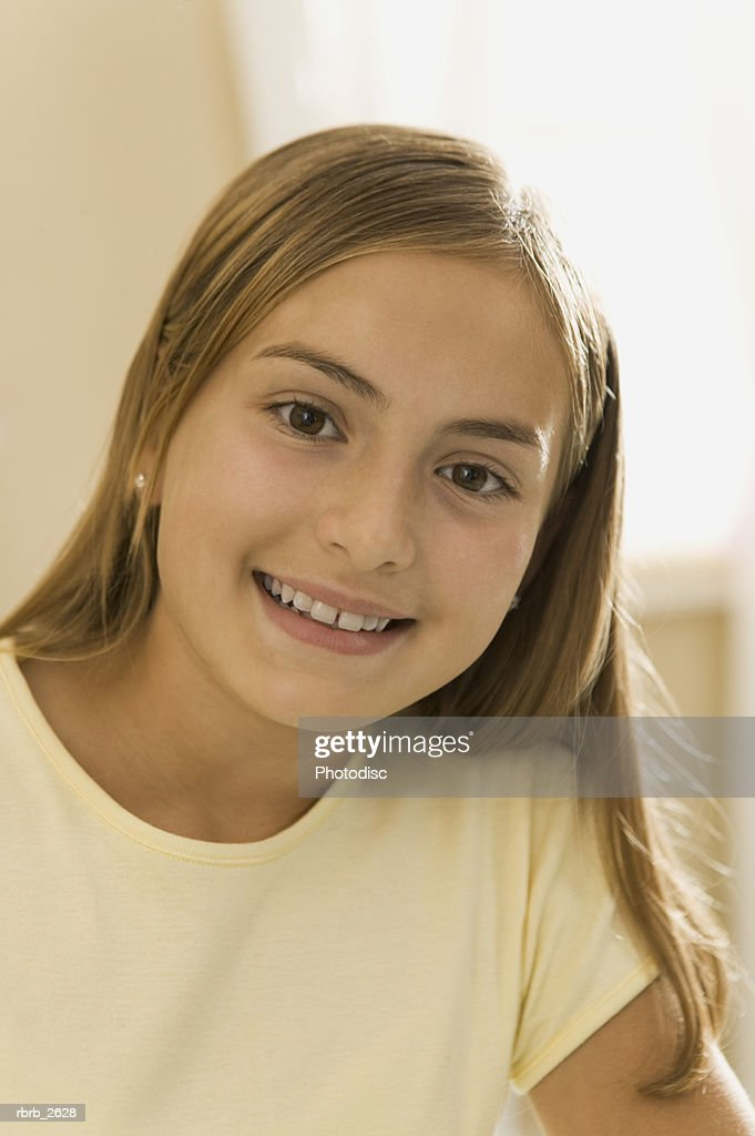 teenage lifestyle shot of a girl in a yellow shirt as she smiles at the camera : Foto de stock