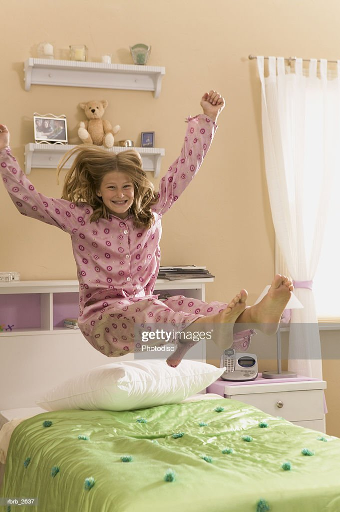 teenage lifestyle shot of a girl in pink pajamas as she bounces on her bed : Foto de stock