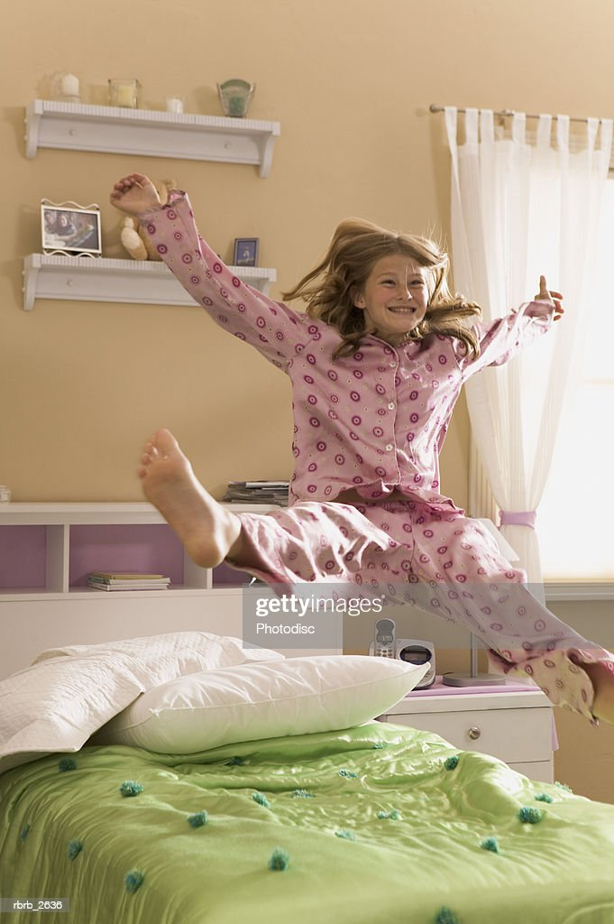 teenage lifestyle shot of a girl in pink pajamas as she bounces up on her bed : Foto de stock