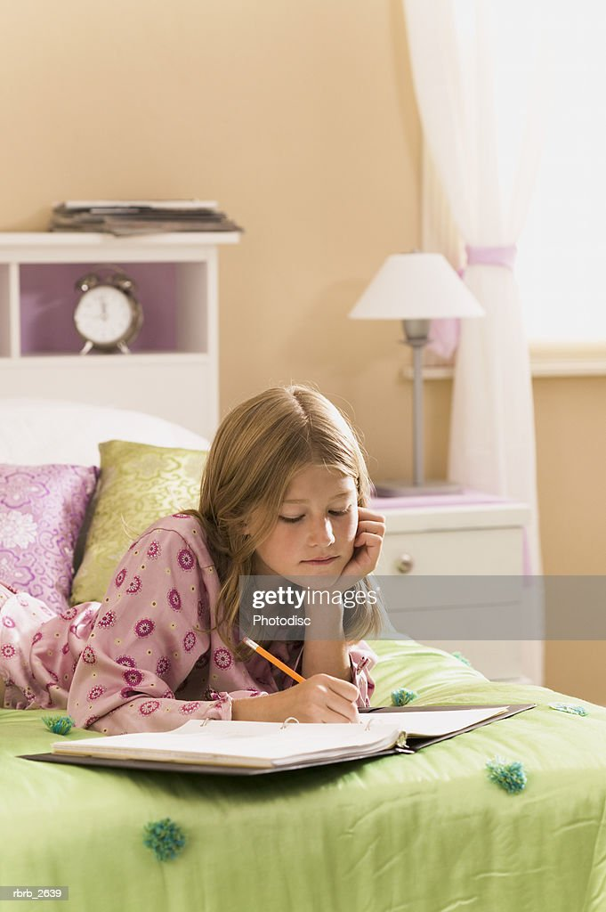 teenage lifestyle shot of a girl in pink pajamas as she does her homework on her bed : Foto de stock