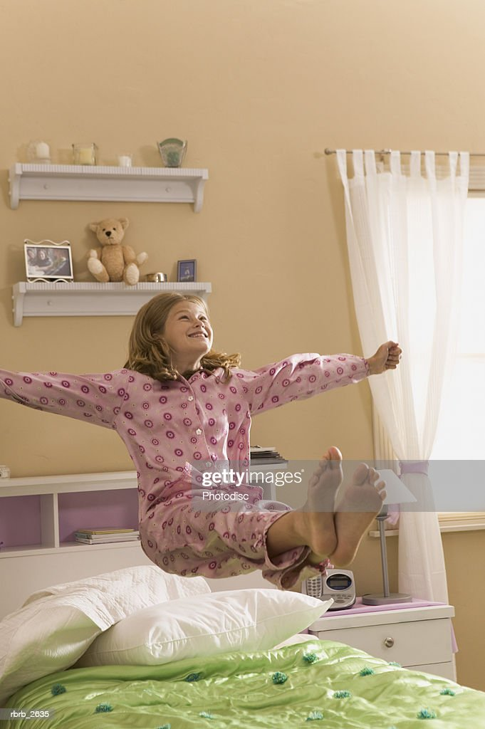 teenage lifestyle shot of a girl in pink pajamas as she jumps and bounces on her bed : Foto de stock