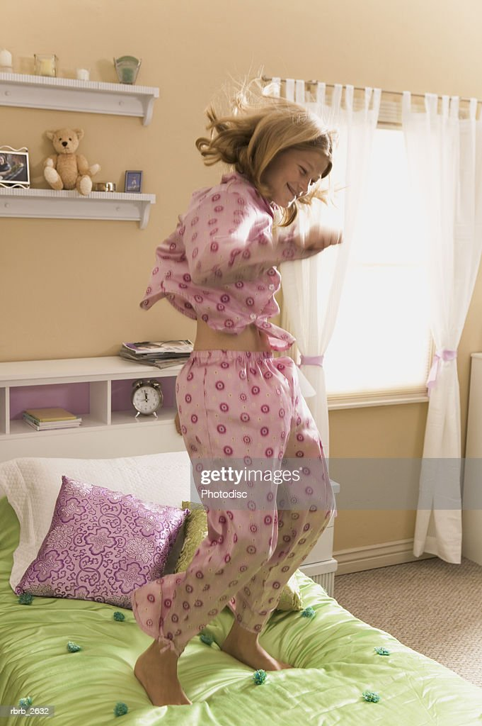 teenage lifestyle shot of a girl in pink pajamas as she jumps on her bed : Foto de stock