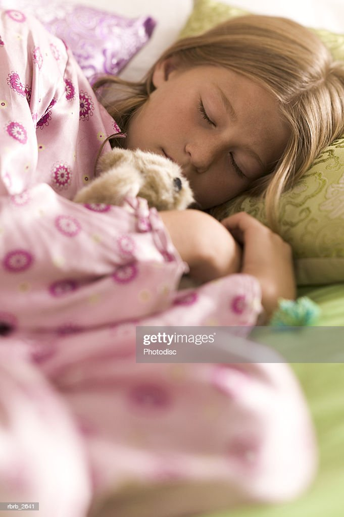 teenage lifestyle shot of a girl in pink pajamas as she lays asleep on her bed : Foto de stock