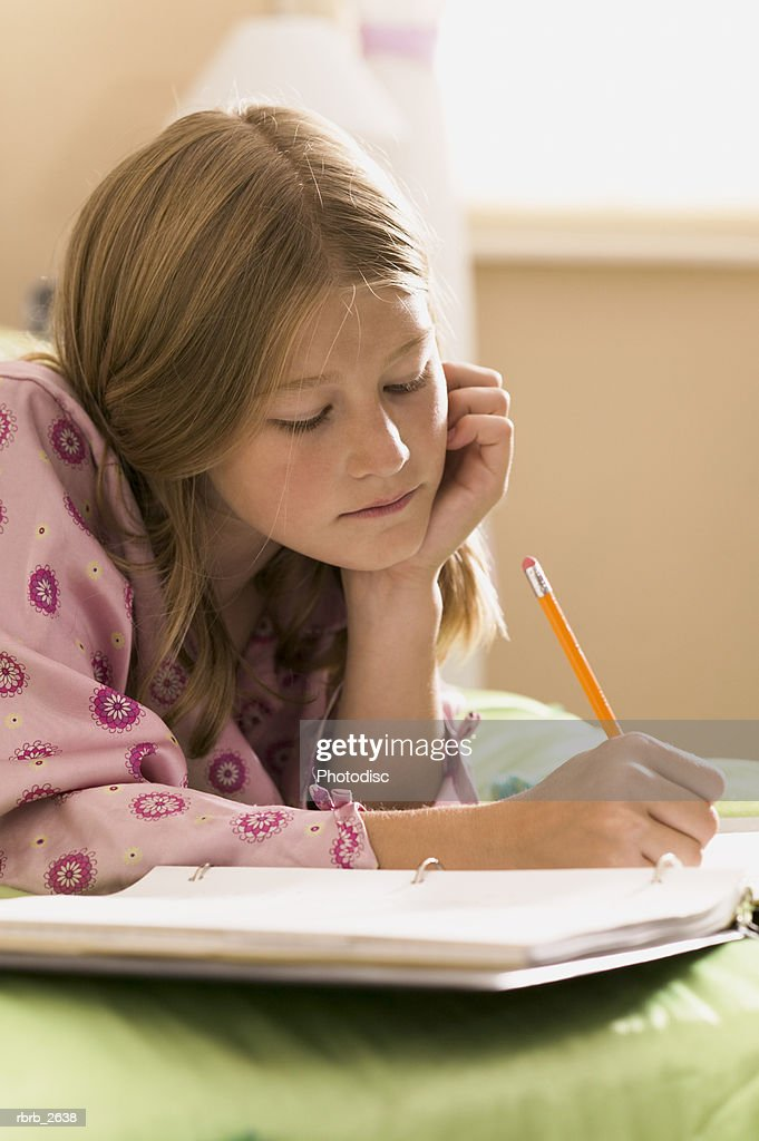 teenage lifestyle shot of a girl in pink pajamas as she lays on her bed doing her homework : Foto de stock