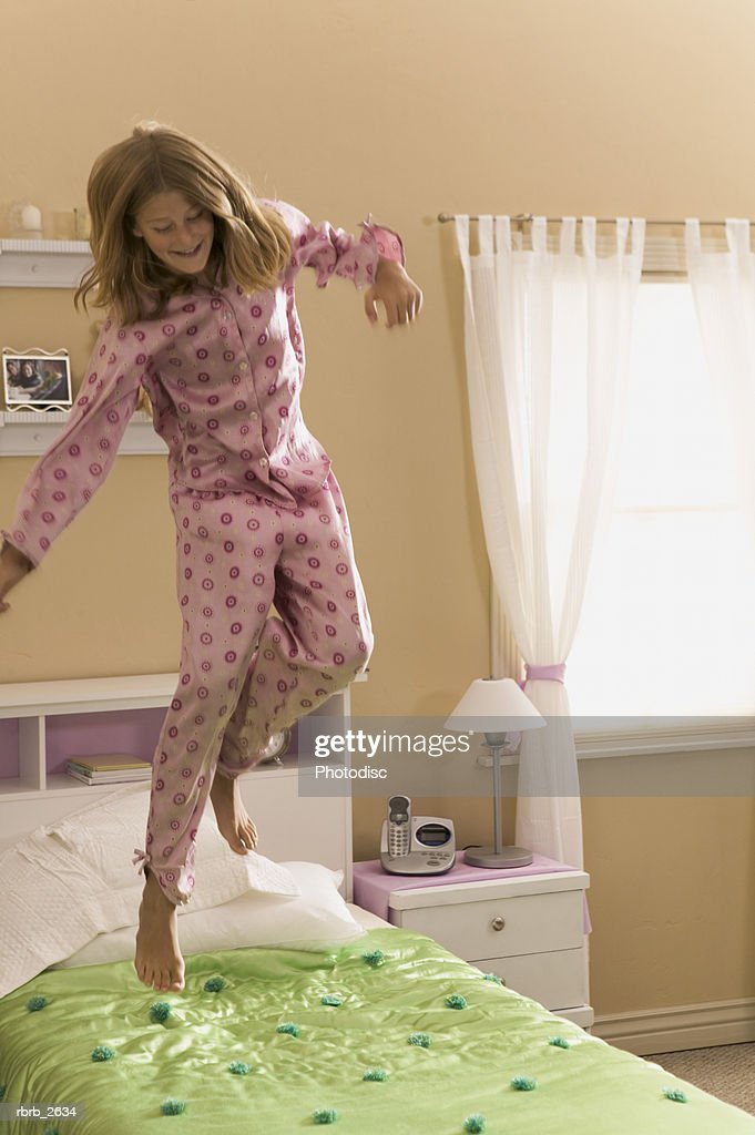 teenage lifestyle shot of a girl in pink pajamas as she playfully jumps on her bed : Stock-Foto